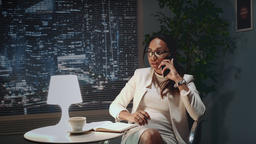 African american business woman in eyeglasses speaking by smartphone with Footage