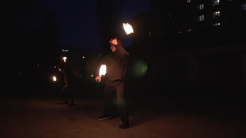Female and male show people in black suits spinning fireballs at night in slo-mo Footage
