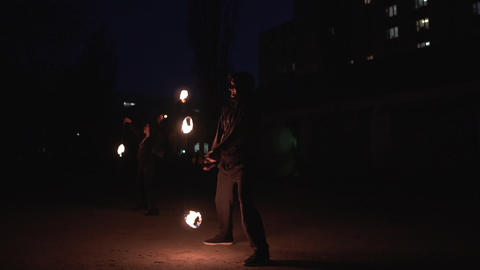 Female and male jonglers in black suits rotating fireballs at night in slo-mo Footage