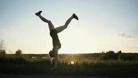 Slim girl does handstand and makes moonwalk in slow motion at sunset Live Action