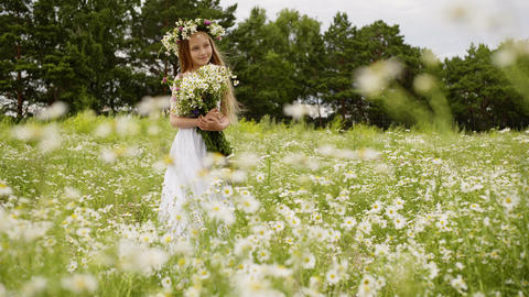 Smiling young girl in wreath with flowers bouquet standing on flowering field Live Action