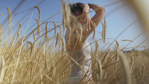 Skill woman wearing bodysuit with short hair on the wheat field. Yellow wheat Live Action