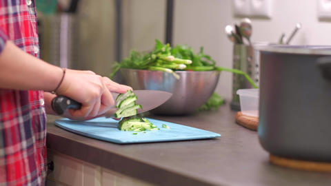 Young housewife slices cucumbers on plastic board Live Action