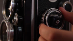 girl's hand twists the focus wheel of a vintage medium format camera Live Action