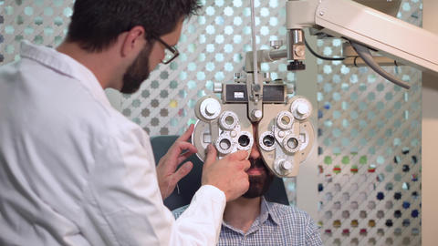 ophthalmologist examining patient with visual inspection device. male. Patient Live Action