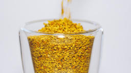 Bee pollen grains are falling down into a glass. Slow Motion Footage