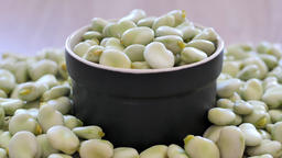 Raw fava beans in a stoneware Live Action