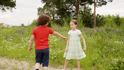 Playful boy and girl walking on grass meadow at summer vacation. Cheerful Live Action