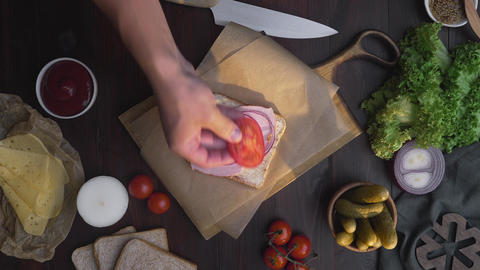 Flat lay of chef's hand adds slised tomatoes to the sandwich with sliced ham and Live Action
