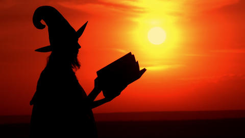 outdoors silhouette witch holding big magic book Live Action