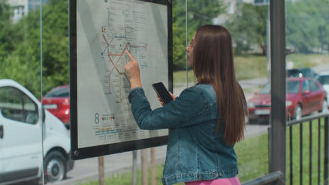 Woman looking on the scheme of public transport while standing at the tram Live Action