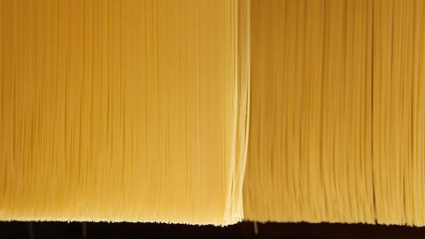 Closeup of raw spaghetti folding in a pasta factory Live Action