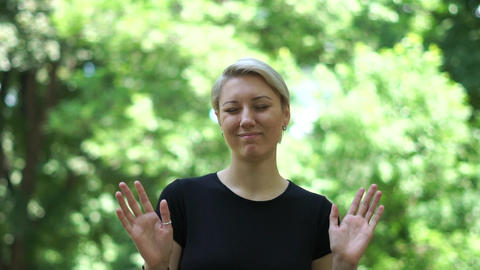 Attractive woman does not trust the words waving her hands in park in slo-mo Live Action