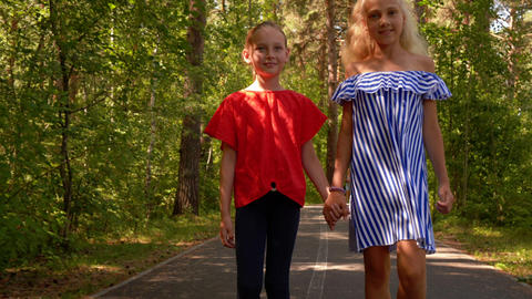 Two girlfriends holding hands walking in summer park. Happy teenager girls Live Action