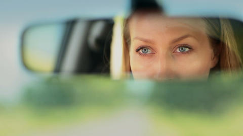 Reflection of woman's blue eyes in rearview mirror Footage