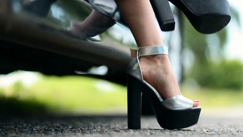 Closeup view of woman's legs getting out of car Footage