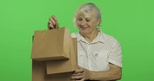 An elderly woman with shopping bags. Shopping. Presents. Chroma key Footage