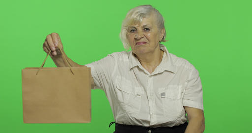 An elderly woman with shopping bag. Shopping. Presents. Chroma key Footage