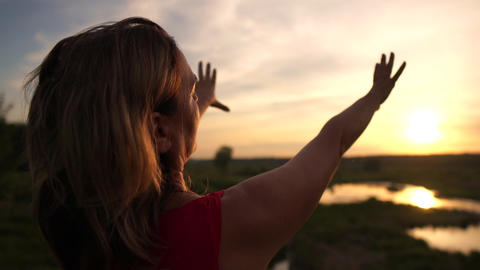 Inspired woman doing a heart gesture at small sedge lake at sunset in slo-mo Live Action