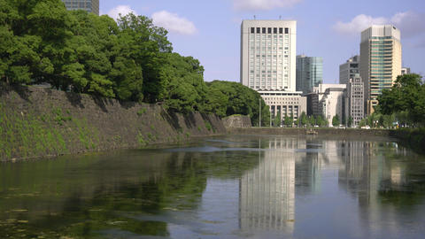 Tokyo,Japan-July 27,2019: Water in moat reflecting buildings in Tokyo Live Action