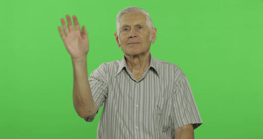 Senior man waving hands to camera. Handsome old man on chroma key background Footage