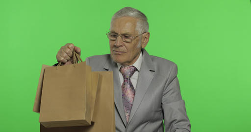 Elderly businessman with shopping bags. Old man in formal wear after shopping Footage