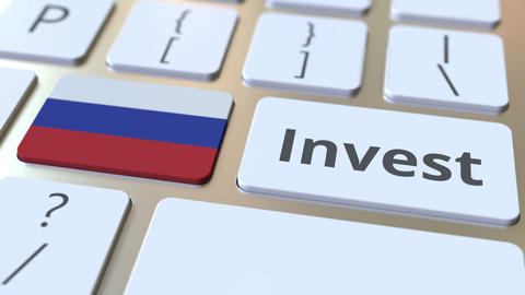 INVEST text and flag of Russia on the buttons on the computer keyboard. Business Live Action