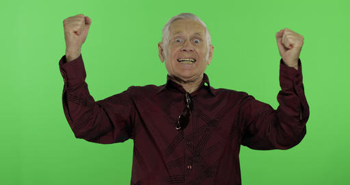 Senior man something emotionally celebrating. Handsome old man on chroma key Footage