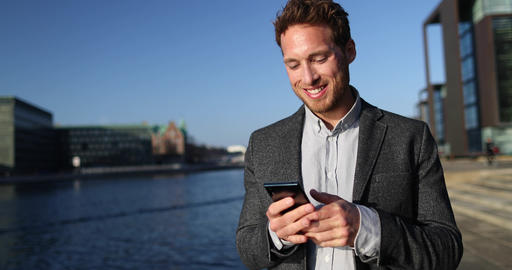 Business man Using Smartphone App in Big City Business District Street Live Action