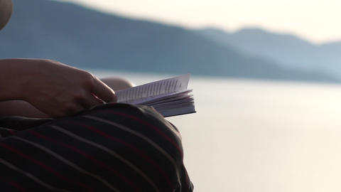 The woman reading a book near the sea, hands close up in slow motion at sunrise Footage