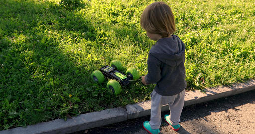 Kid playing with car on remote control Live Action