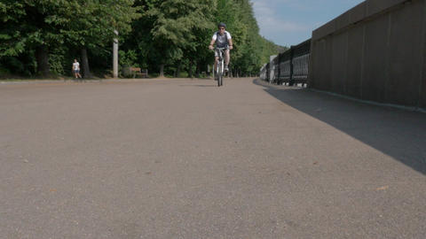 male cyclist passes by the camera, view from a low point, moves to the camera Live Action