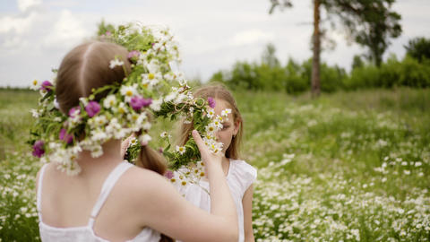 Teen girl puts wreath to her friend head walking at flower meadow at summer Live Action