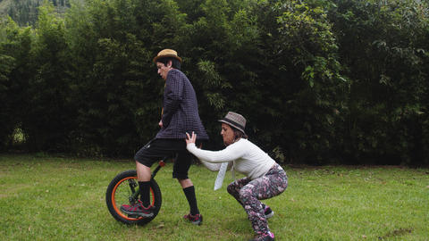 Stylish Couple Having Issues With A Monocycle In Their Backyard In Ecuador Live Action