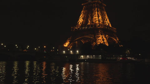 Paris, France, 20 May 2019 - Eiffel Tower illuminated at twilight with the Seine Footage