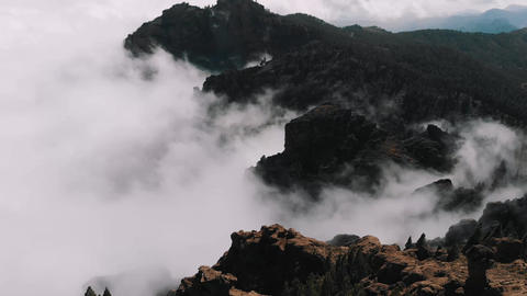 Aerial view - beautiful clouds curl in the gorges of the mountains, view from a Footage