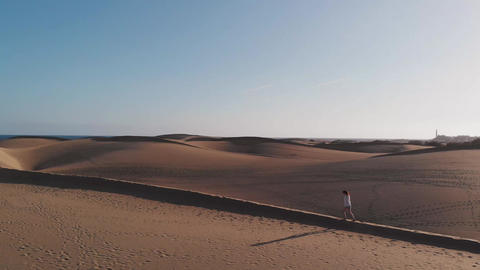 Aerial view is a side view of the dune along which a beautiful young woman walks Footage