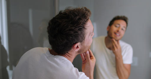 Man face care looking in mirror touching his beard or skin health - male beuaty Live Action