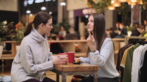 emotional lady talks with friend at small table in cafeteria Live Action
