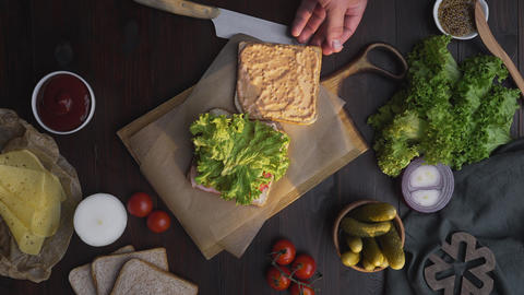 Flat lay of the sandwich with ham and salad on the wooden board in the beam of Live Action