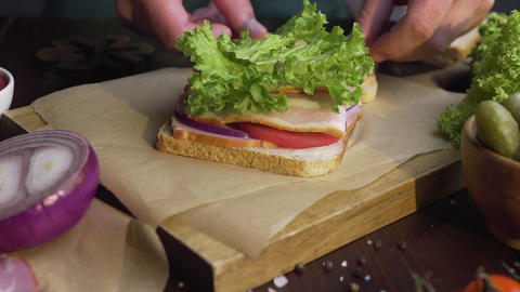 Chef finalizes the sandwich with ham and salad on the wooden board in the beam Live Action