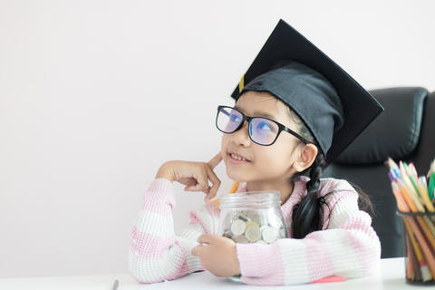 Little Asian girl wearing graduate hat putting the coin into clear glass jar 015 フォト