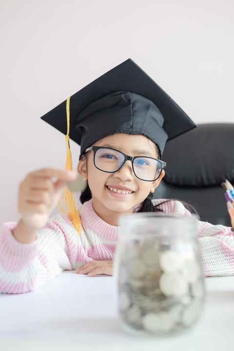 Little Asian girl wearing graduate hat putting the coin into cle フォト