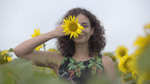 Pretty curly playful smiling girl standing on the sunflower field. Bright yellow Live Action