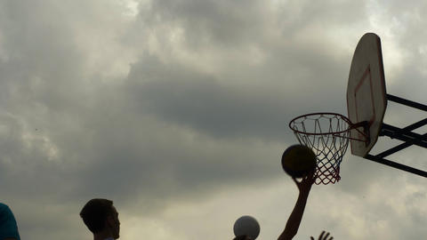 Sportsman throwing basketball ball in hoop outdoor. Basketball player throwing Live Action