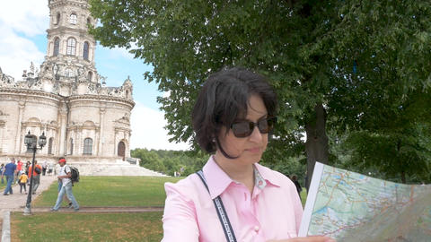 brunette woman looks at paper map against the background of a historic building Live Action