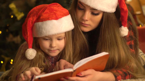 Older Sister Read Together With The Younger, The Girls Read The Book. Christm Live Action