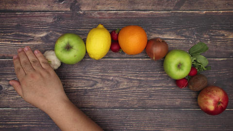 Fruits and vegetables appear under the man's hand on wooden background - Stop motion Animation