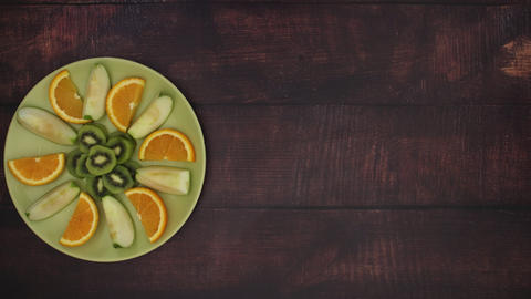 Green plate with fruits going across desk - Stop Motion Animation