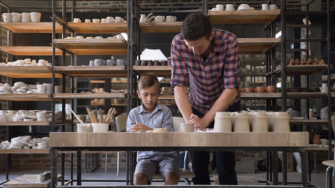 Caring male potter teaching his son how kneading clay for pots Live Action